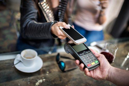 person making a purchase with a smart phone above payment terminal